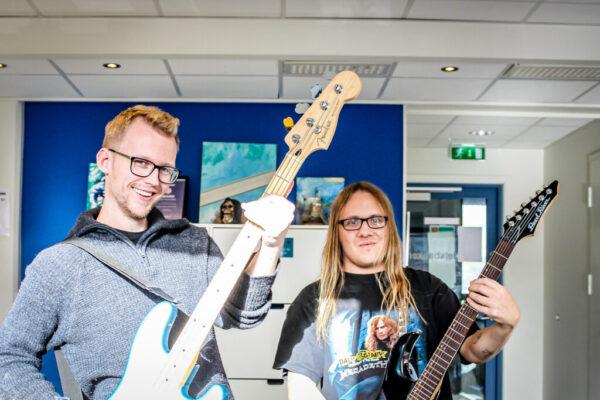 To menn som holder en gitar hver (bilde)