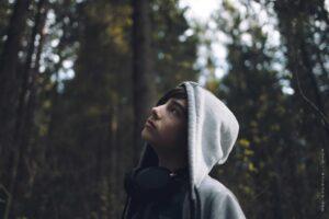 Ung gutt med hettegenser står i skogen og kikker opp (bilde)