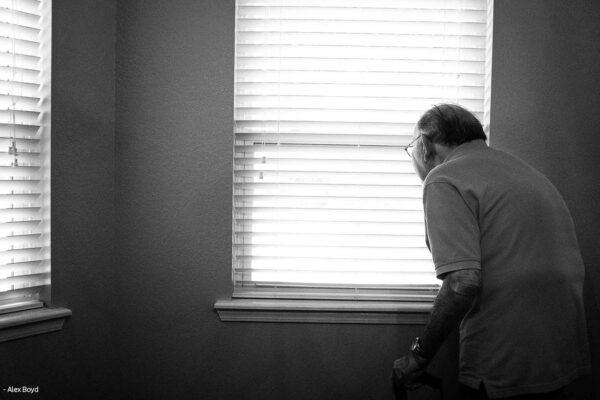 Eldre mann kikker ut av vindu (image)
