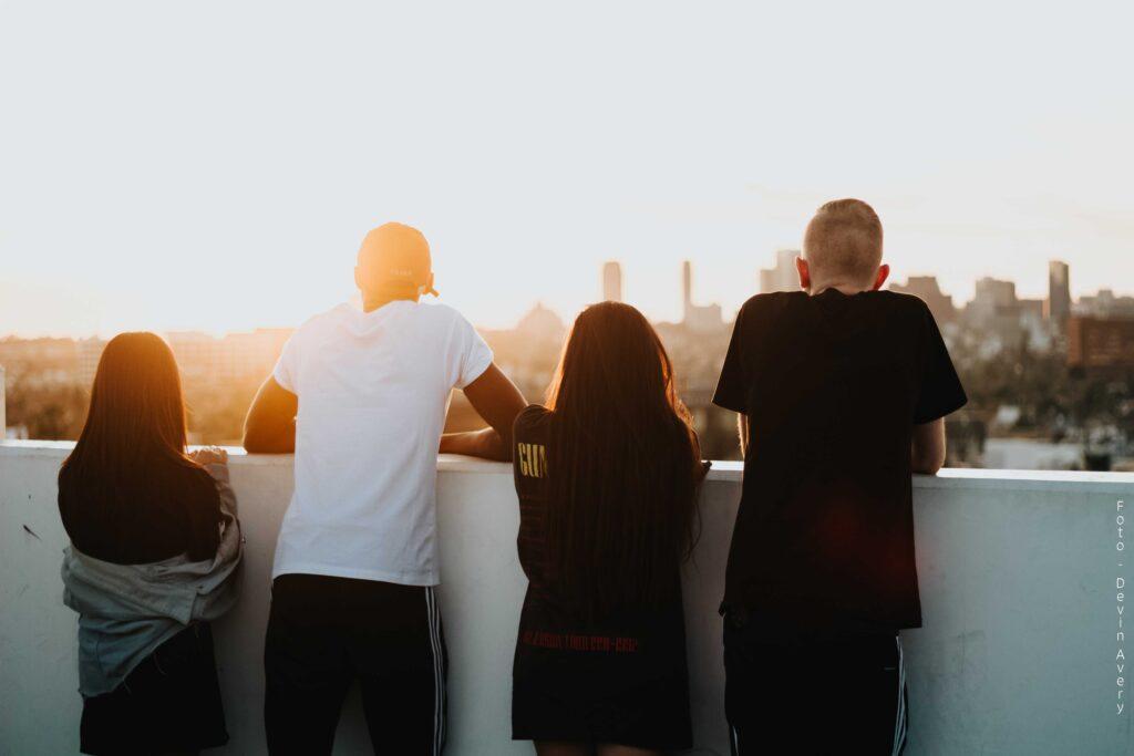 Fire ungdommer står med ryggen til og kikker ut over et bylandskap (image)