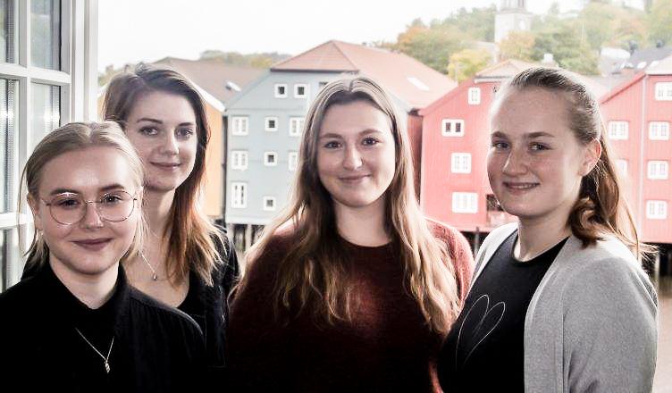Fire jenter kikker i kamera, bryggerekka i Trondheim i bakgrunnen (image)