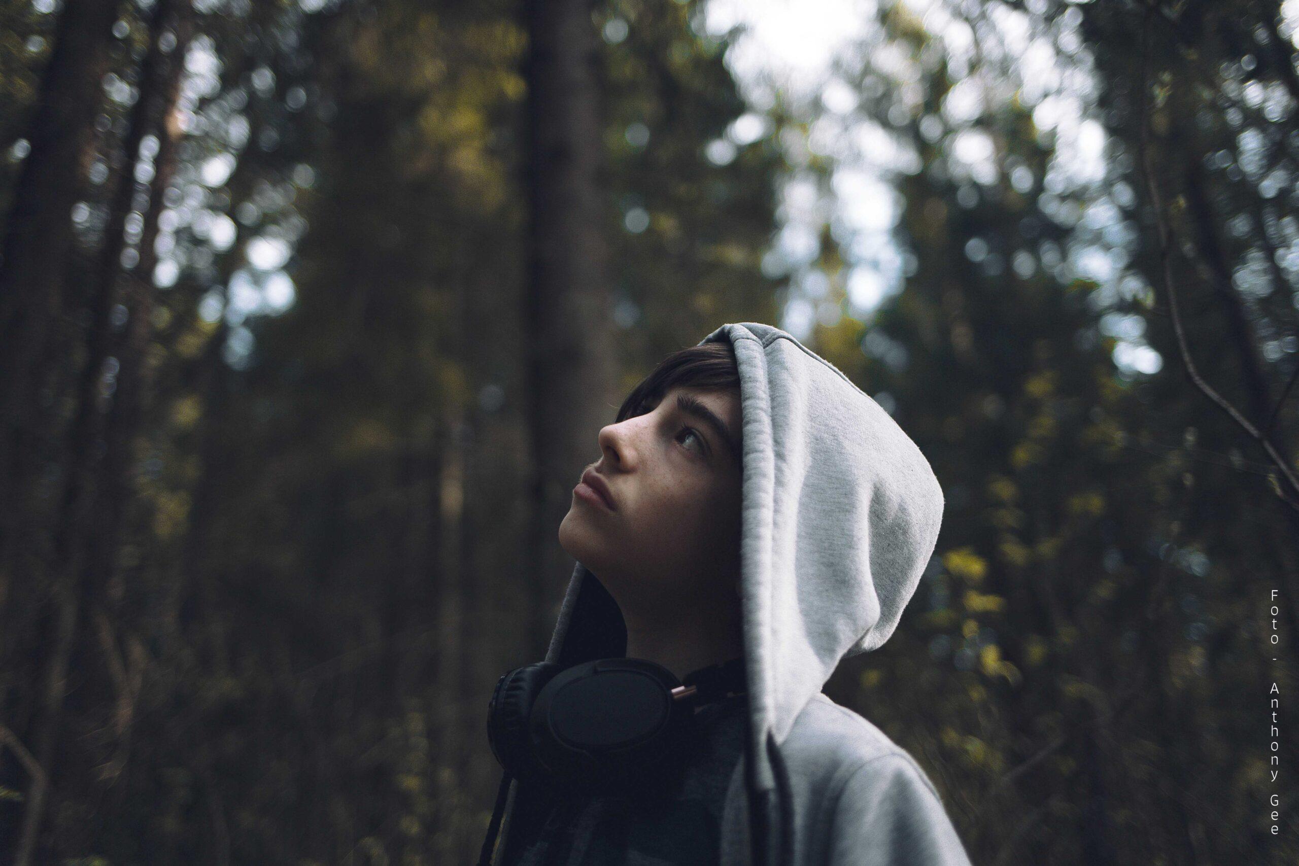 Ung gutt i hettegenser som ser opp mot himmelen