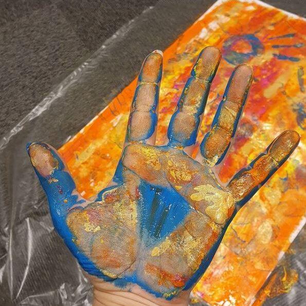 Hånd med maling i mange farger (bilde)